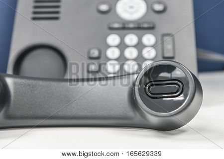 IP Phone handset is holding the call on the white table