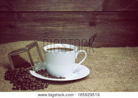 White cup of coffee standing on the sackcloth. Around it are scattered coffee beans and ground coffee glass Wooden desk on the background fills a half of the photo. Edited as a vintage photo.