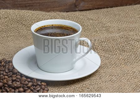 White cup of coffee is standing on the sackcloth. Around it are scattered coffee beans and ground coffee glass. Wooden desk on the background.