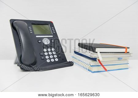 Black IP Phone and stack of books