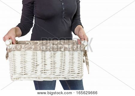 Standing woman is holding white empty basket. All is isolated on the white background.