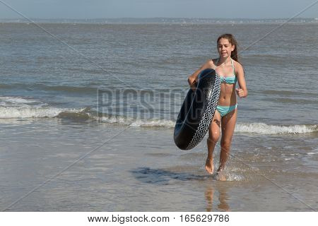 Young Girl Returns From Bathing With Her Buoy On The Beach