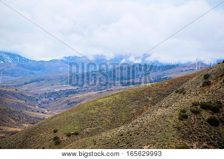 Barren and desolate High Desert terrain with mountains beyond taken during a winter storm in Tehachapi Pass, CA
