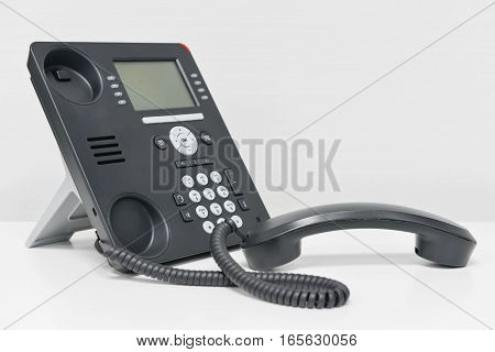 Black IP Phone and handset on the white table