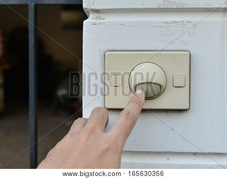 Human hand push the doorbell at the front home