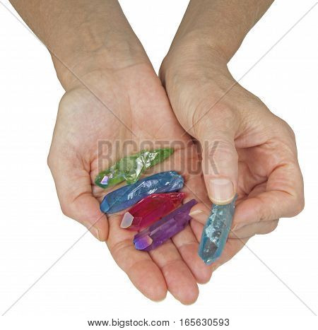 Crystal Therapist Holding Aura Terminated Quartz Wands - female crystal therapist holding and offering a  selection of brightly colored aura quartz wands isolated on a white background