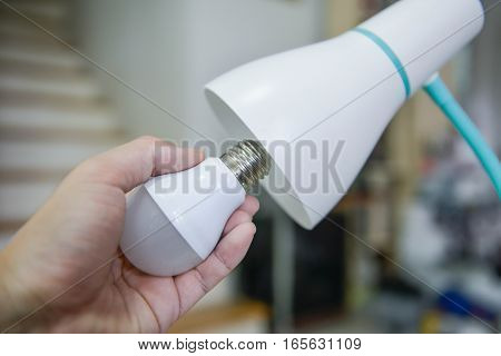 Man hand changing the LED bulb to white lamp - Saving energy concept