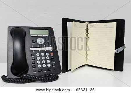 Black IP Phone and opened notebook on the white table