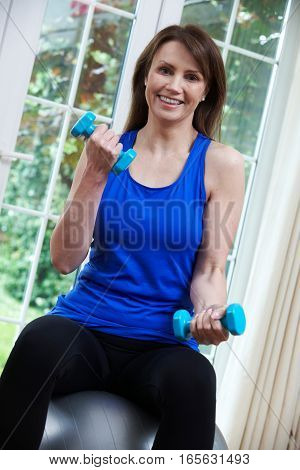Mature Woman Exercising With Swiss Ball And Weights At Home