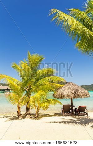 Two sunlounger chairs under a thatched parasol on a sand beach with a view on the lagoon and Mount Otemanu on the tropical island of Bora Bora near Tahiti in French Polynesia. Vertical composition