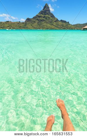 Female crossed legs over tropical blue lagoon and Otemanu mount Bora Bora near Tahiti in French Polynesia. Vertical composition
