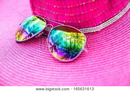 Pink summer hat and colorful sunglasses with palm tree reflection close up