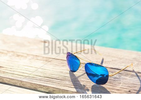 Blie Sunglasses on wooden decking by seaside