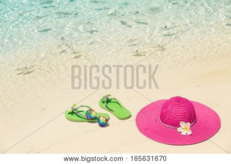Pink beach hat sunglasses and green slippers in the golden sand by sea shore