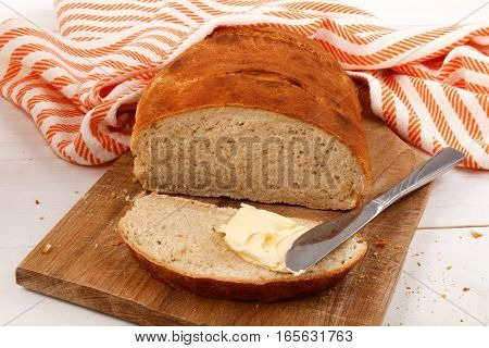 freshly baked warm slice bread with irish butter and knife on wooden board