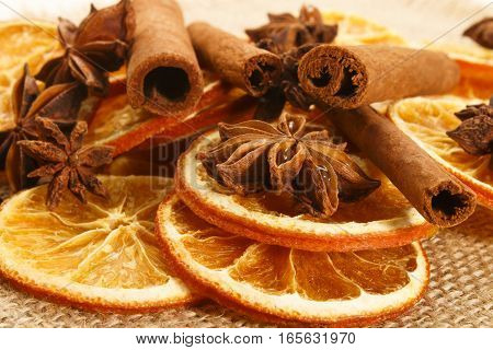 dried orange slices with anise and cinnamon sticks on brown jute
