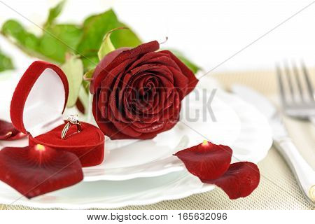 Table setting for a romantic dinner with Gold engagement ring with diamonds in an elegant velvet box and a red rose.