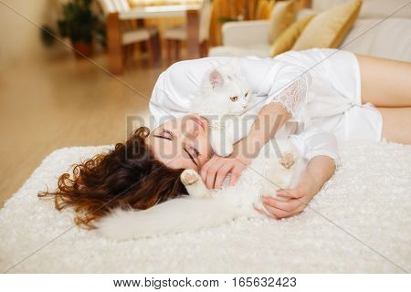 Beautiful curly hair girl in a white silk dressing gown in the early morning playing with white fluffy cat sitting on sofa