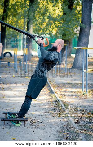 Muscular bearded man doing body weight resistance training with straps outdoors in the park