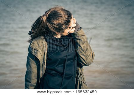 Outdoor portrait of a teenage girl wearing khaki parka and hiding her face. Toned effect