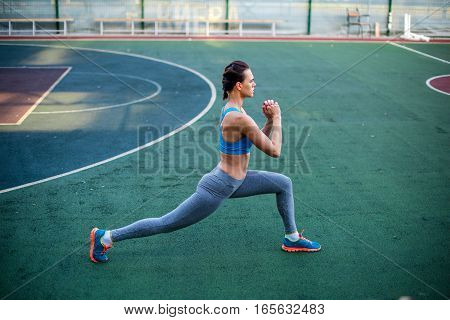 Side view of woman in sportswear training on stadium