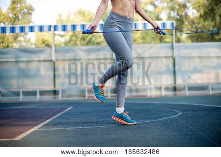 Cropped shot of woman in sportswear jumping rope at stadium