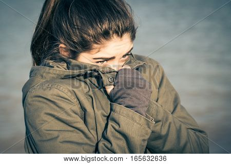 Outdoor portrait of a teenage girl wearing khaki parka and hiding her face from the wind. Toned effect