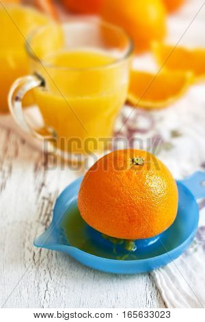 Plastic juicer with glass of fresh orange juice on white rustic wooden background