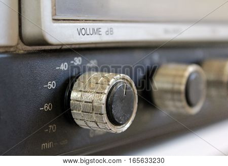 Close up of volume knob button on vintage stereo, color.