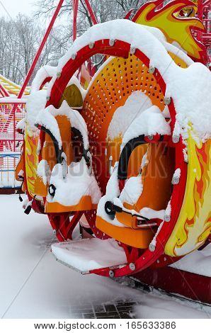 Colorful children's attraction covered by snow in winter park during snowfall Gomel Belarus