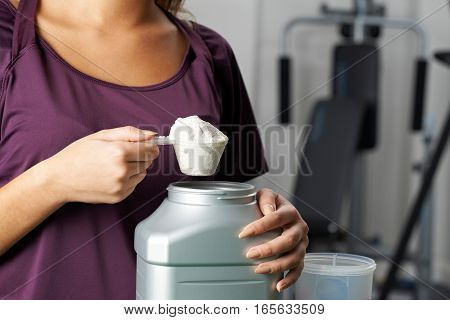Young Woman In Gym Taking Nutritional Supplement
