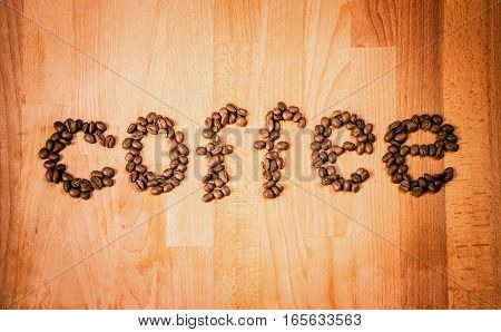 Coffee beans on wood background. Shape of word Coffee made from coffee beans on wooden surface. Roasted coffee beans on rustic wood background. Top view..