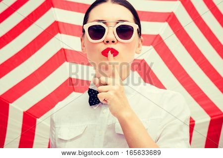 Stylish beautiful woman wearing white chemise and sunglasses with bright painted lips showing secret gesture next to a striped background