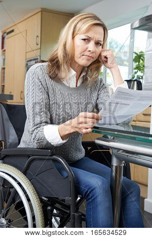 Portrait Of Frustrated Woman In Wheelchair Reading Letter