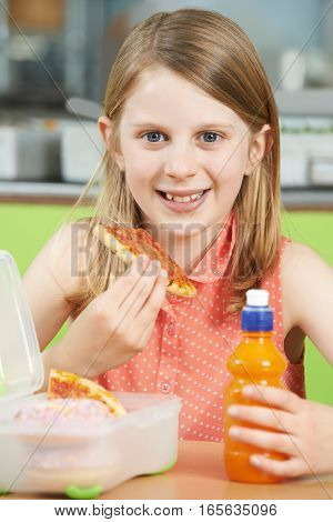 Female Pupil Sitting At Table In School Cafeteria Eating Unhealthy Packed Lunch