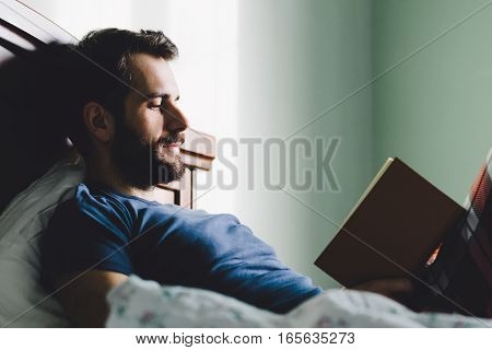 Young man reading a book in his bedroom