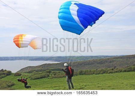 paragliders launching off the coast of Wales