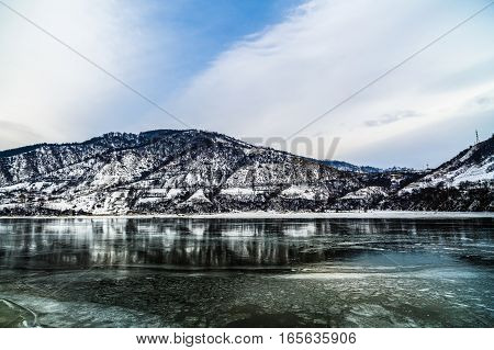 Winter landscape with mountains reflected in the river