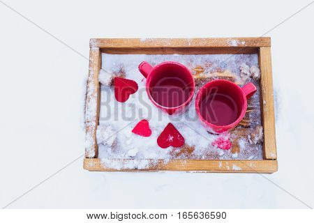 Two red cups with tea on a wooden tray in snow. Romantic Valentine's day winter picnic hot tea couple. Lifestyle time together outdoors Valentine's day. Snowflakes hoarfrost and heart shape on a tray