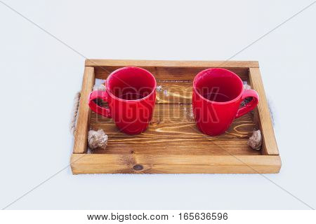 Two red cups with tea on a wooden tray in snow. Romantic winter picnic couple going to drink hot tea. Lifestyle winter walk time outside. Snowflakes and hoarfrost on a tray