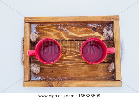 Overhead shot of two red cups with tea on a wooden tray in snow. Romantic winter picnic couple going to drink hot tea. Lifestyle winter walk time outside. Snowflakes hoarfrost on a tray