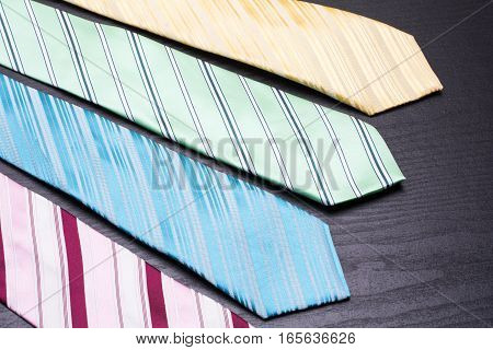 Four lined colorful ties on black table