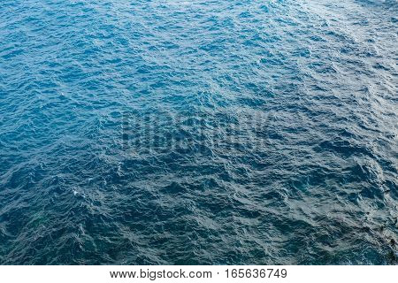 a clear blue colored water surface on the open sea with small waves, the colors are in a gradient from dark to light cyan.