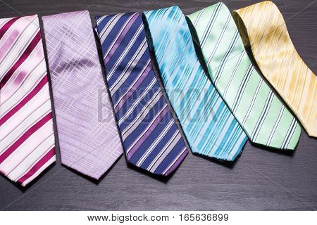 Several lined colorful ties on black table