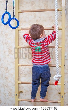 The child climbs up the stairs. Gymnastics children's sports Swedish wall.