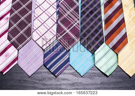 A lot of lined colorful ties on black table