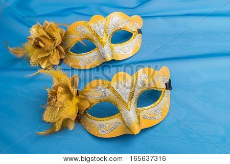 Yellow Carnival mask on satin blue background.