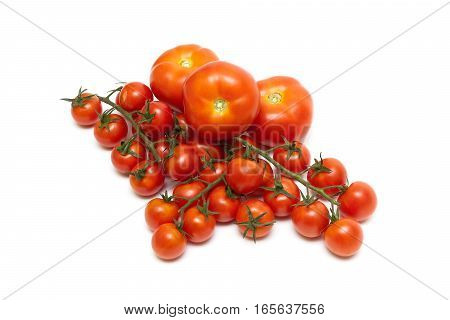 ripe tomatoes and a bunch of cherry tomatoes on a white background. horizontal photo.