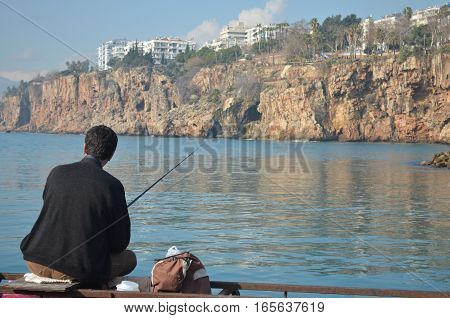 fisherman sitting on the shore of the sea in front of rocks and cliffs with fishing rod in his hands