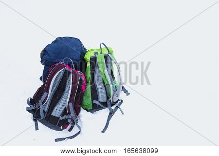Three hiking backpacks in snow. Adult and kids backpacks isolated on white background. Copy space. Family hiking on beautiful cold winter day. Snowlakes on backpacks.